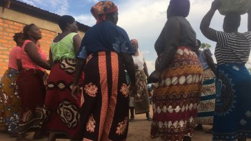 Malawian women stand in a cirlce wearing colorful chitenje cloth skirts and carrying buckets on their heads.