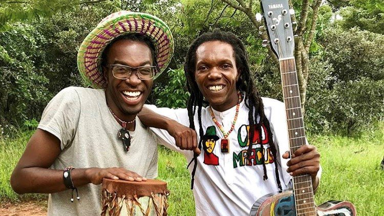 A black American male plays music with his friend from Tanzania