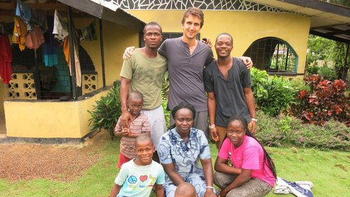 Joe stands with his Liberian family