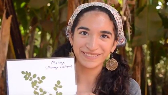 A female Volunteer holds a picture of moringa and smiles.