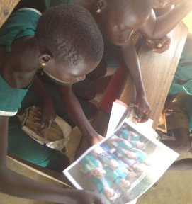 Girls in Ghana look at a picture of their Girl Scout pen pals in California.