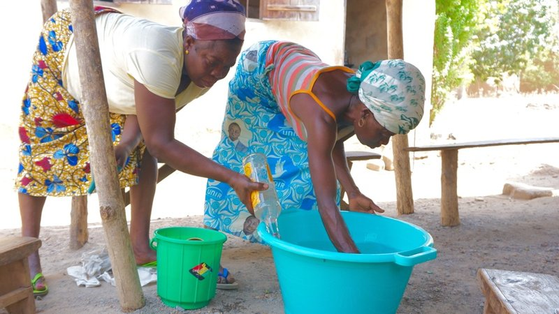 Bitho adds water to the soap mixture while Kotoko stirs.  The process takes about one hour spread over two days and is much easier with a group of women.