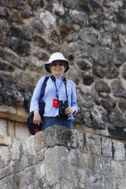 Carolyn standing near the top of a Mayan pyramid at Uxmal enjoying views of Green Jays and an Altamira Oriole.