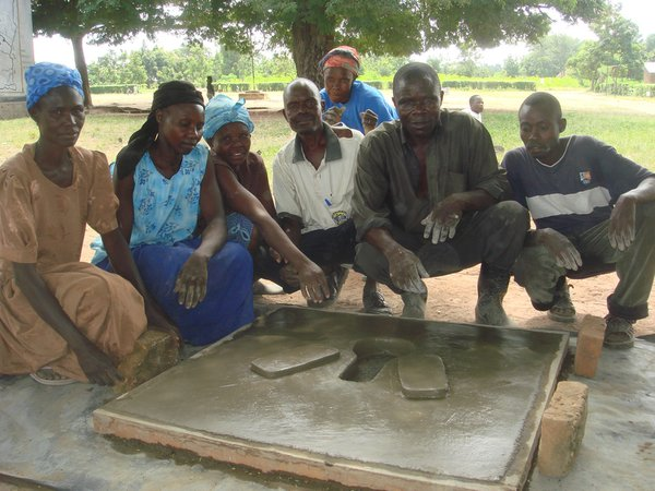 Uganda: Volunteer health team with the completed cement pit latrine.