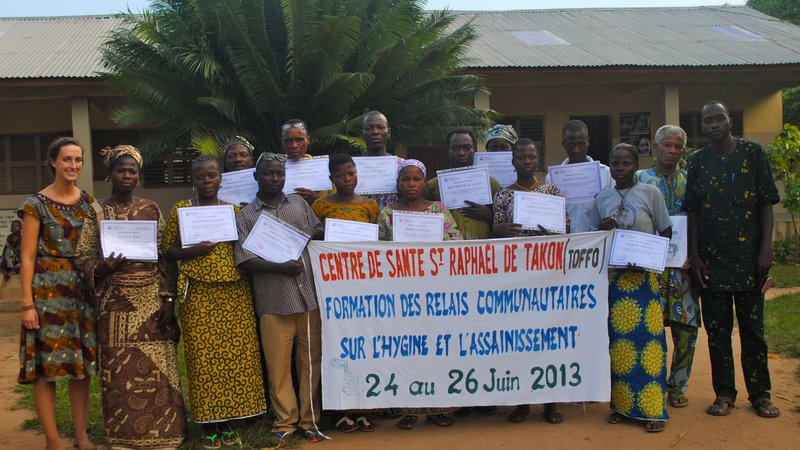Returned Peace Corps Volunteer Rachel Leeds poses with a group of community health worker in Benin, following the completion
