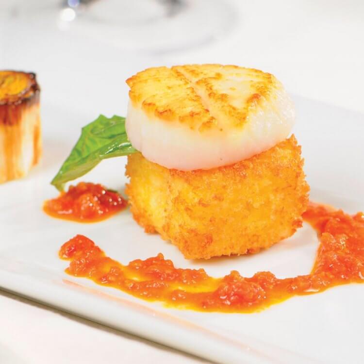 Palet de risotto croustillant au cidre et Le 1608, pétoncles et poireaux juste grillés, sauce au pesto de tomates séchées et câpres
