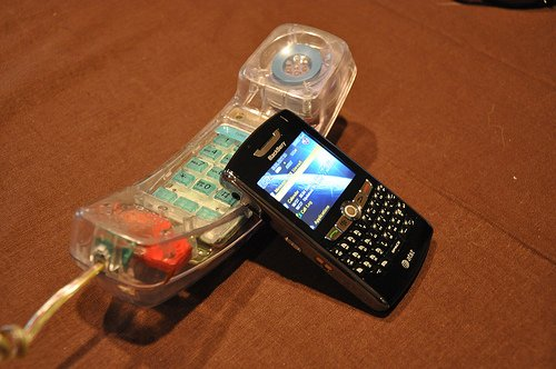 An old Blackberry leaning against an older see-thru touch-tone phone.